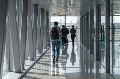 Pasażery iść wzdłuż lotnisko mostu wsiadać samolot obraz stock