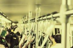 Pasażery stoi na pociągu podczas godzina szczytu i używa handlebar pracować w, publicznie transport, Podczas gdy podróż fotografia royalty free