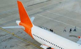 Pasażery wyokrętują od spaceru na asfalcie w kierunku śmiertelnie budynku i samolotu zdjęcia royalty free
