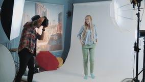 Pasado de la sesión fotográfica: bella modelo rubia posando para una foto de una revista de moda metrajes