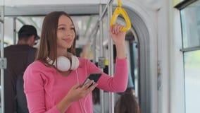 Pasajero de la mujer joven que disfruta de viaje en el transporte público, colocándose con smartphone en la tranvía moderna almacen de metraje de vídeo