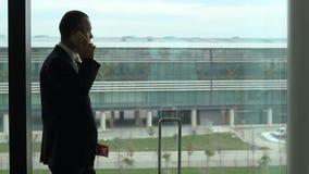 Pasajero del hombre de negocios en el aeropuerto por la ventana que habla con el teléfono almacen de metraje de vídeo
