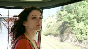 Pasajero femenino joven dentro del tren que mira hacia fuera la ventana en el camino Retrato de la mujer morena sensual con almacen de metraje de vídeo