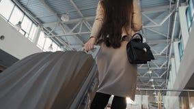 Pasajero femenino joven en el aeropuerto, con su tableta mientras que espera su vuelo caminando en terminal metrajes
