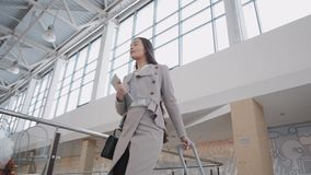 Pasajero femenino joven en el aeropuerto, con su tableta mientras que espera su vuelo caminando en terminal almacen de video