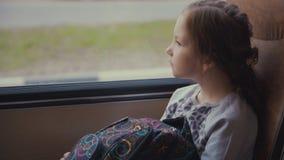 Pasajero joven, hermoso de la muchacha con el bolso de escuela en el autobús escolar móvil que mira hacia fuera la ventana Imágenes de archivo libres de regalías