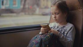 Pasajero joven, hermoso de la muchacha con el bolso de escuela en el autobús escolar móvil usando red social en su smartphone y Imagen de archivo