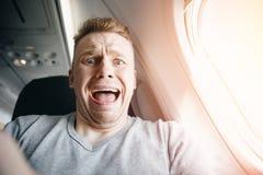 Pasajero masculino en los gritos y los gritos planos, aerophobia fondo de la porta Miedo del concepto del vuelo en el aeroplano imagenes de archivo