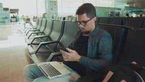 Pasajero masculino que se sienta en pasillo que espera en aeropuerto y SMS que manda un SMS por smartphone metrajes