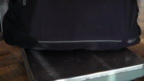 Pasajero que comprueba el peso del equipaje con la escala almacen de video