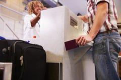 Pasajero que pesa el equipaje en el incorporar del aeropuerto Imágenes de archivo libres de regalías