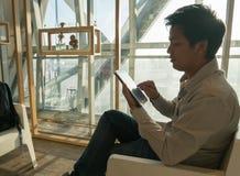 Pasajero que usa la tableta en aeropuerto Foto de archivo libre de regalías