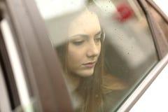 Pasajero triste del coche que mira a través de ventana Imágenes de archivo libres de regalías