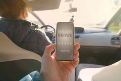 Pasajero usando el app elegante del teléfono para valorar un taxi o a un par moderno para mirar conductor ridesharing fotografía de archivo libre de regalías