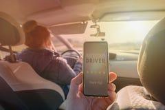 Pasajero usando el app elegante del teléfono para valorar un taxi o a un par moderno para mirar conductor ridesharing imagen de archivo