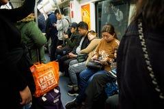 Pasajeros a bordo de un carro apretado del subterráneo del metro de Shangai foto de archivo libre de regalías
