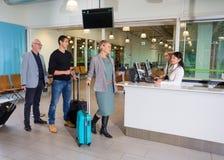 Pasajeros con el equipaje que espera en la recepción del aeropuerto Fotografía de archivo