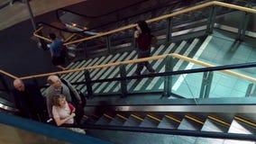 Pasajeros con el equipaje que toma la escalera móvil dentro del aeropuerto de YVR almacen de video