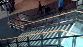 Pasajeros con el equipaje que toma la escalera móvil dentro del aeropuerto de YVR metrajes