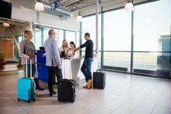 Pasajeros con la situación del equipaje mientras que recepcionistas que trabajan en Foto de archivo