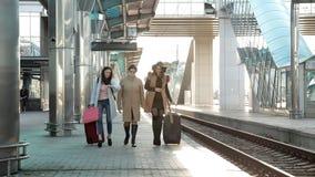 Pasajeros con las maletas que caminan en la plataforma del ferrocarril Tres mujeres con las maletas que caminan en metrajes