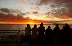 Pasajeros del barco de cruceros que toman cuadros de la puesta del sol Imagenes de archivo