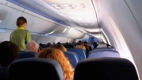 Pasajeros dentro de la cabina de los aviones de pasajero que se sientan en las sillas durante el vuelo metrajes