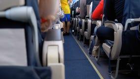 Pasajeros dentro de la cabina de los aviones de pasajero que se sientan en las sillas durante el vuelo almacen de metraje de vídeo