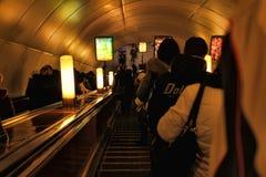 Pasajeros en la escalera móvil en el metro Imágenes de archivo libres de regalías
