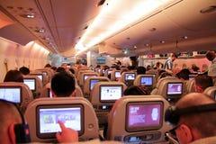Pasajeros en un vuelo de la economía que muestra los asientos y las pantallas táctiles foto de archivo libre de regalías