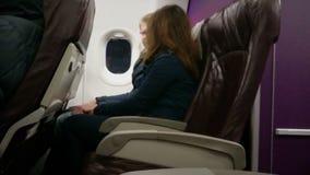 Pasajeros masculinos y femeninos que consiguen conocidos, hablando durante vuelo en el avión almacen de metraje de vídeo