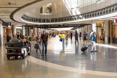 Pasajeros que caminan con el lugagge en aeropuerto Fotos de archivo libres de regalías