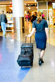Pasajeros que caminan con equipaje en un aeropuerto Fotografía de archivo libre de regalías