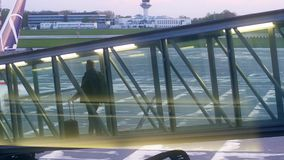 Pasajeros que caminan en un puente de cristal del jet metrajes