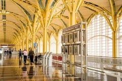 Pasajeros que caminan a través de un aeropuerto brillante Foto de archivo libre de regalías
