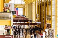 Pasajeros que caminan a través de un aeropuerto brillante Fotografía de archivo libre de regalías