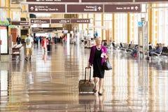 Pasajeros que caminan a través de un aeropuerto brillante Imagen de archivo