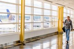 Pasajeros que caminan a través de un aeropuerto brillante Fotos de archivo libres de regalías