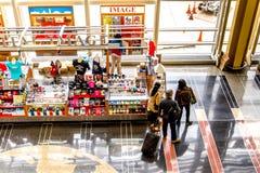 Pasajeros que caminan a través de un aeropuerto brillante Imagen de archivo libre de regalías