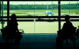 Pasajeros que esperan en la puerta de salida aeroplano de embarque fotografía de archivo