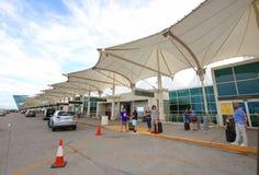 Pasajeros que esperan para ser cogido en el aeropuerto imagenes de archivo