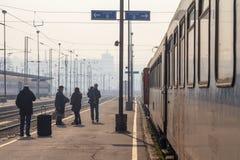 Pasajeros que esperan para subir a un tren en la plataforma de la estación de tren principal de Belgrado durante una tarde solead fotos de archivo libres de regalías