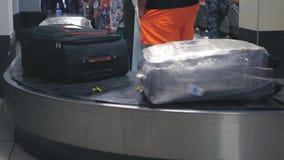 Pasajeros que esperan su equipaje, que viaja a lo largo de la cinta 4k, 3840x2160, HD almacen de metraje de vídeo