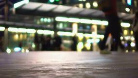 Pasajeros que esperan transporte en la estación iluminada, siluetas defocused almacen de video