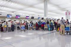 Pasajeros que hacen cola para arriba en contador de enregistramiento en Hong Kong International Airport Imagenes de archivo