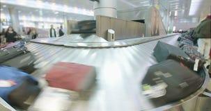 Pasajeros que recogen el equipaje de una banda transportadora en el aeropuerto almacen de metraje de vídeo