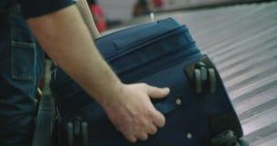 Pasajeros que recogen el equipaje de una banda transportadora en el aeropuerto metrajes