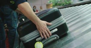 Pasajeros que recogen el equipaje de una banda transportadora en el aeropuerto almacen de video