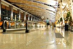 Pasajeros que recorren en una terminal de aeropuerto Fotos de archivo libres de regalías