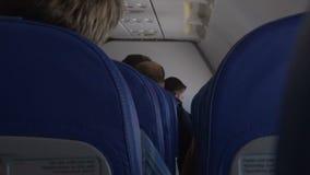 Pasajeros que se sientan en cabina del aeroplano y que hablan, transporte, turismo almacen de video